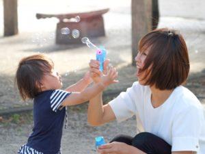シャボン玉で遊ぶ子供と母親