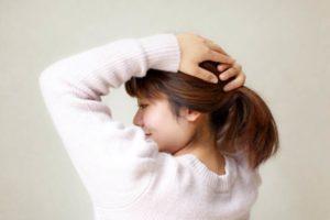 後ろ髪をかきあげる女性
