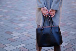黒のバッグを後手に持つ女性