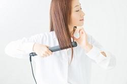 ヘアアイロンをかけるロングヘアの女性