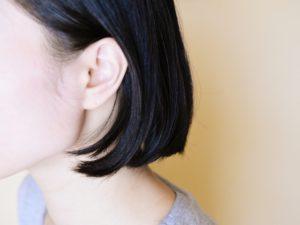 横髪を耳にかけたショートヘアの女性