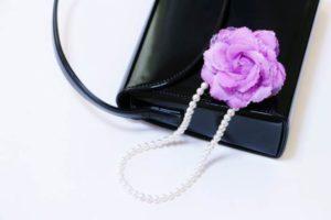 黒の本革バッグ ピンクのコサージュ パールのネックレス