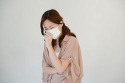 マスクを付けて咳をする風邪気味の女性