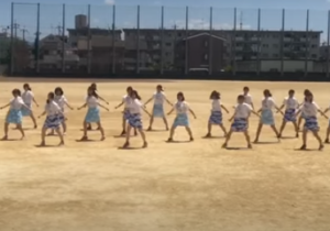 校庭でダンスする女子学生