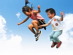 青空にジャンプする女の子と男の子