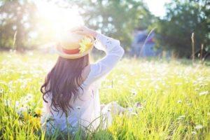 草原び座る麦わら帽子をかぶった女性