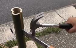 ハンマーとナタで竹を半分に切る