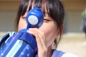 水筒の飲み物を飲む女子