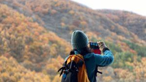 登山中に紅葉の山の写真を撮る女性