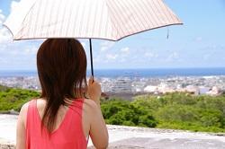 日傘をさして街並みを眺める女性