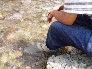 川に足を浸すサンダルを履いた男性