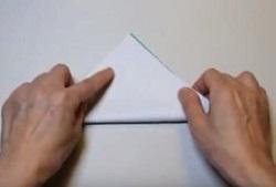 緑の折り紙を三角形に半分に折る