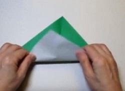 緑の折り紙を三角形に折る