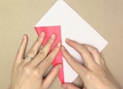 赤い折り紙を線に沿って折る