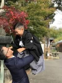 紋付袴の男の子と高い高いするお父さん