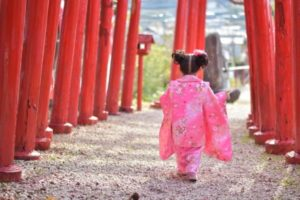 鳥居の下を歩く着物姿の女の子