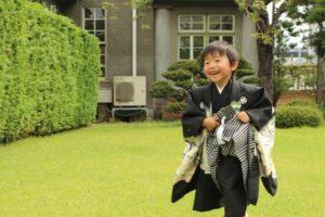 芝生の上を駆ける着物を着た男の子