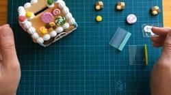 牛乳パックで作った家 紙粘土で作ったお菓子を貼り付けていく