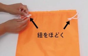 オレンジ 巾着袋 紐をほどく