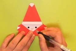 折り紙で作ったサンタさんに顔を描く