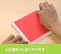 赤い折り紙の上の端を折る