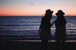 海岸で日の出を見る二人の女声