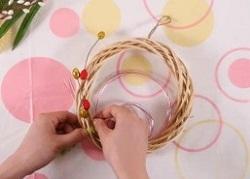 リースに正月飾りの後ろの部分からマスキングテープで固定していく