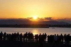 海辺で初日の出を見る人々