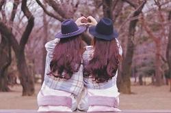 二人の女性 手でハート 公園のベンチ
