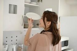 食器棚からお皿を取り出す女性