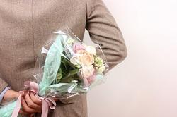 花束を後手に持ったスーツ姿の男性