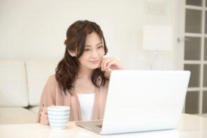 女性 ノートパソコン コーヒーカップ