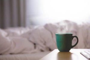 ホテルのベッドとコーヒーカップ