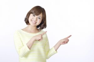 両手でポイントポーズの笑顔の女性