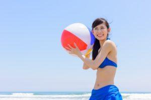 海辺 ビーチボールを持った水着の女性