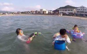 海の中 水鉄砲で遊ぶ子供たち