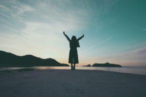 海岸で朝日に向かって両手を広げる女性