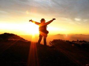 山頂で両手を広げて日の出を迎える女性