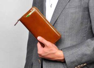 革の財布を持つスーツを着た男性